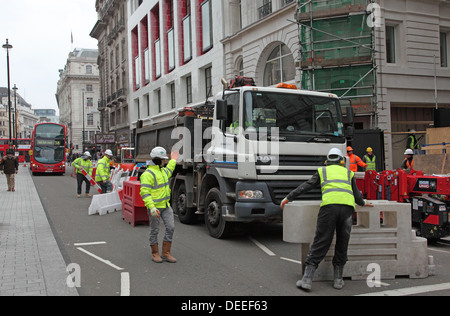 A lorry is maneuvered into place as roadworks cause disruption to traffic and pedestrians on London's Piccadilly - Stock Photo
