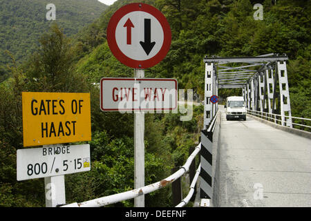 Caravan on one-lane bridge over Gates of Haast, right of way sign, yield. Haast Pass. New Zealand - Stock Photo