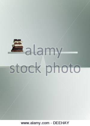 Chocolate bars balanced on seesaw - Stock Photo