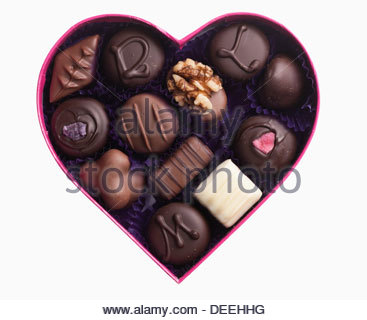 Close up of chocolates in heart-shape box - Stock Photo