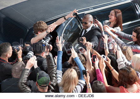 Celebrity emerging from limo towards paparazzi - Stock Photo