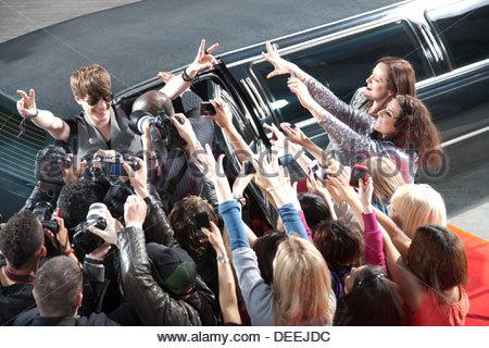 Celebrity emerging from limo towards paparazzi - Stock Photo