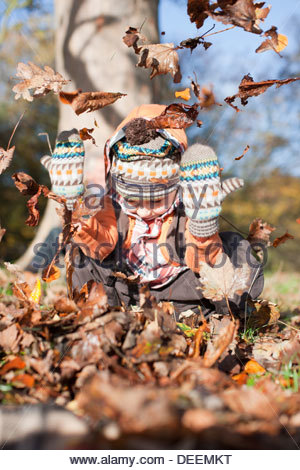 Boy playing in pile of autumn leaves - Stock Photo