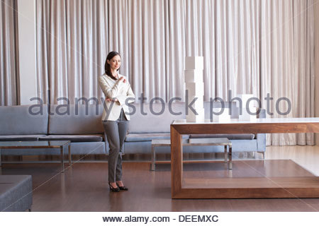 Businesswoman stacking white cubes in hotel lobby - Stock Photo
