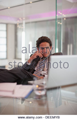 Businessman sitting at desk with laptop - Stock Photo