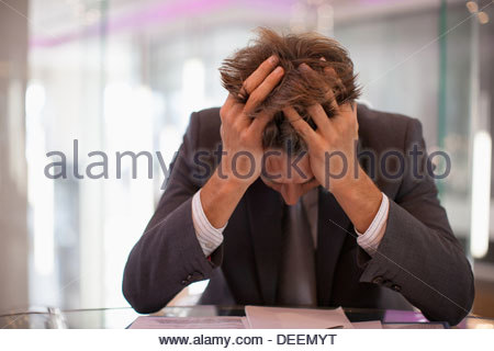 Frustrated businessman sitting at desk with  head in hands - Stock Photo