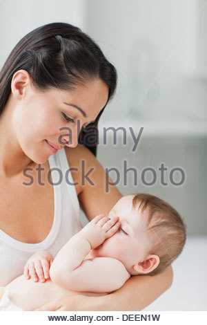 Close up of mother holding sleeping baby sucking thumb - Stock Photo
