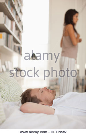 Man laying in bed smiling with wife in background - Stock Photo