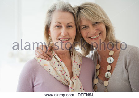 Smiling sisters hugging - Stock Photo