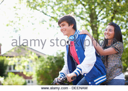 Teenage boy riding girlfriend on bicycle - Stock Photo