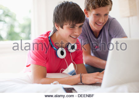 Teenage boys using laptop together - Stock Photo