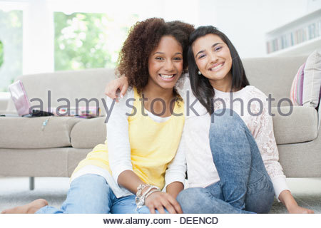 Smiling teenage girls hugging - Stock Photo