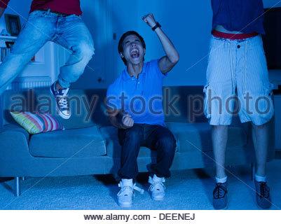 Shouting teenage boys watching television - Stock Photo