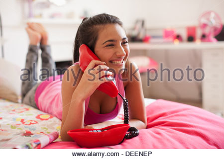 Teenage girl talking on telephone in bedroom - Stock Photo