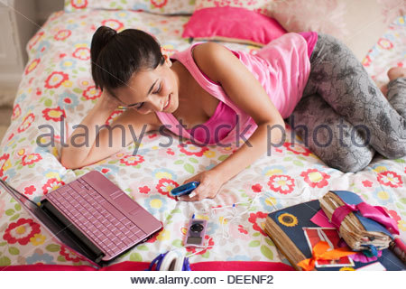 Teenage girl laying on bed text messaging on cell phone - Stock Photo