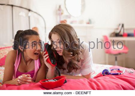 Teenage girls talking on telephone in bedroom - Stock Photo