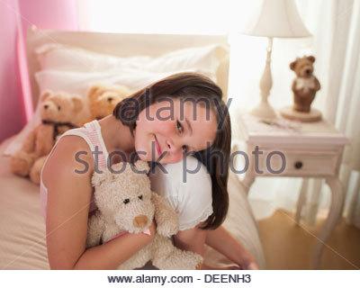 Girl hugging stuffed animal on bed - Stock Photo