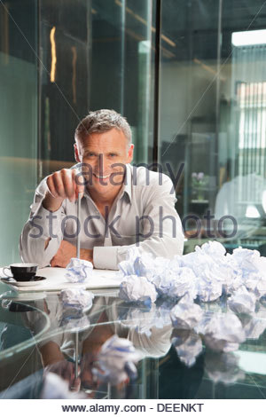 Businessman sitting with crumpled papers in an office - Stock Photo