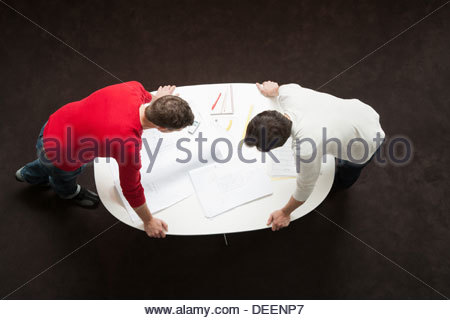 Two businessmen leaning over a table with drafts and paperwork - Stock Photo