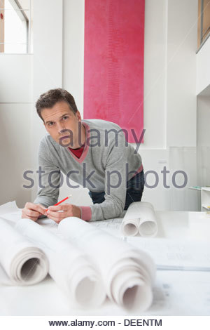 Architect working on drafts in office - Stock Photo