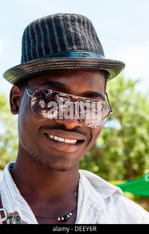 Africa, Angola, Benguela. Portrait of young man in hat and sunglasses. - Stock Photo