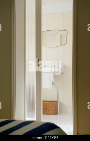View through sliding door to paneled en suite bathroom - Stock Photo