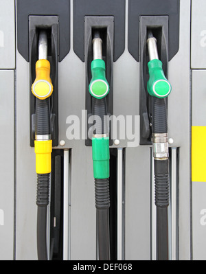 Yellow and green Pump nozzles at the gas station - Stock Photo