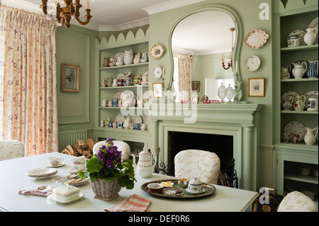 Country house dining room with pottert collection on recessed shelving painted in pastel green - Stock Photo