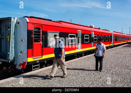 Africa, Angola, Lobito. Men standing beside train. - Stock Photo