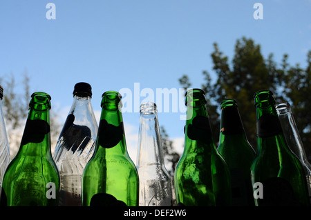Empty green and white bottles waiting to be recycled - Stock Photo