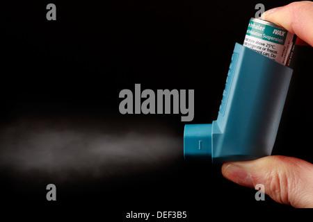 Asthma inhaler being pressed - Stock Photo