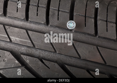 Nail, Screw in a brand new tyre, puncture - Stock Photo
