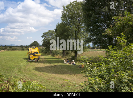 Pilgrims on the GR65 walking route the Way of St James taking shade from the hot sun under tree having a picnic - Stock Photo