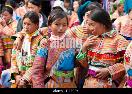 Young women from the Flower Hmong minority ethnic group at the Sunday Morning  Bac Ha Market in Bac Ha, Vietnam. - Stock Photo