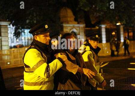 Dublin, Ireland. 18th September 2013. A Garda officer (Irish Police) moves a protester behind the barricades. Protesters - Stock Photo
