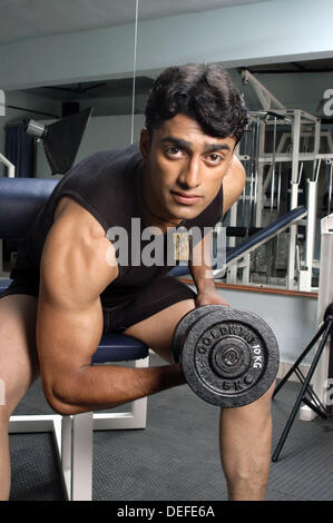 Young man exercising weight training in gym. - Stock Photo
