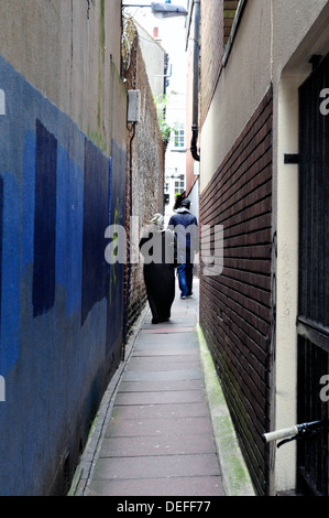 A rear view of a Muslim woman walking in an alleyway, Brighton, UK - Stock Photo