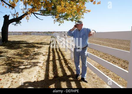 Senior man talks on cell phone by fence and harvested field - Stock Photo