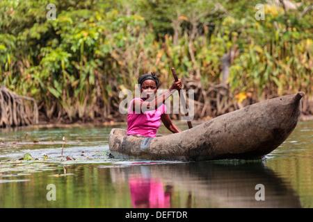 Africa, Liberia, Monrovia. Woman rowing traditional pirogue down Du River. - Stock Photo