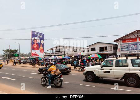 Africa, Liberia, Monrovia. Traffic rushing by busy city market. - Stock Photo