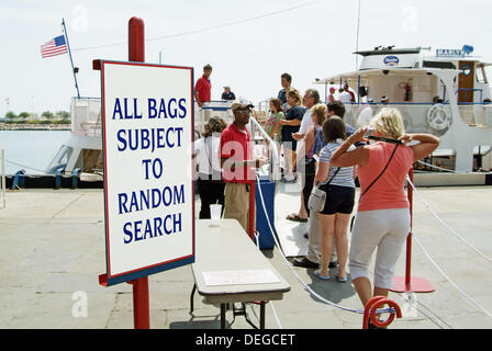 Security checks the bags of tourist before boarding sight seeing boat in downtown Chicago Illinois. USA. - Stock Photo