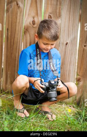 boy looking at his camera - Stock Photo