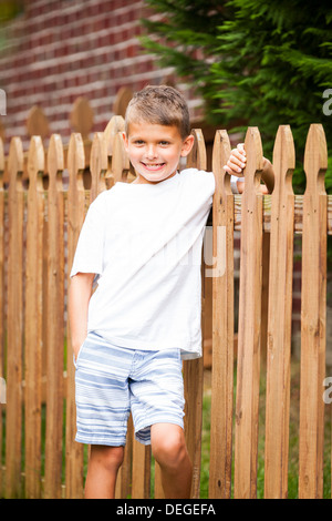 boy leaning on a wooden fence - Stock Photo