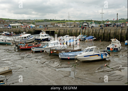 Fishing and leisure boats resting on the mud at low tide in West Bay Harbour, near Bridport in Dorset, May - Stock Photo
