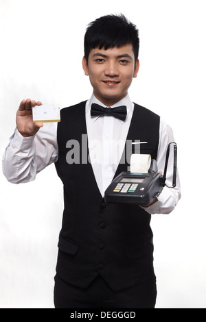 Waiter showing credit card and pos machine - Stock Photo