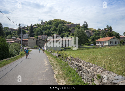 Pilgrims walking through the small village of Montbonnet on the GR65 walking route the Way of St James in France - Stock Photo