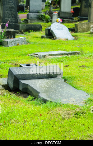 Headstones in a graveyard deliberately laid flat for safety reasons after becoming unstable - Stock Photo