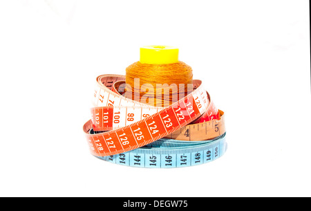 Three tape measures coiled around roll of cotton - Stock Photo
