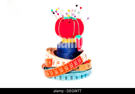 Three tape measures coiled around roll of cotton with Pin Cushion - Stock Photo