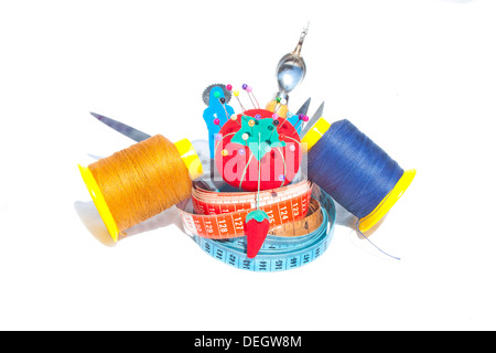 Three measuring tapes with reels of cotton and sewing accessories - Stock Photo
